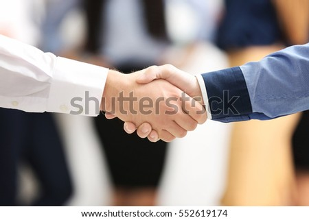 Handshaking of business partners on blurred people background