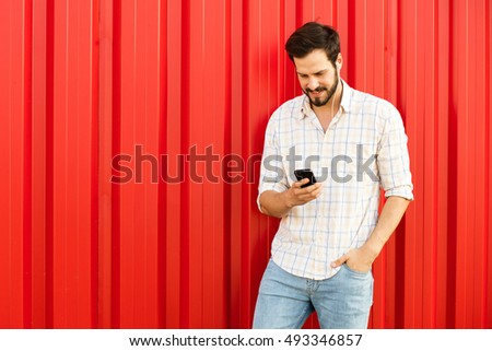 handsome adult man using his cellphone to text somebody, smiling on red background with free space on the side