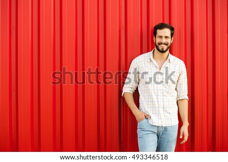 handsome adult man with beard smiling and being relaxed on red wall