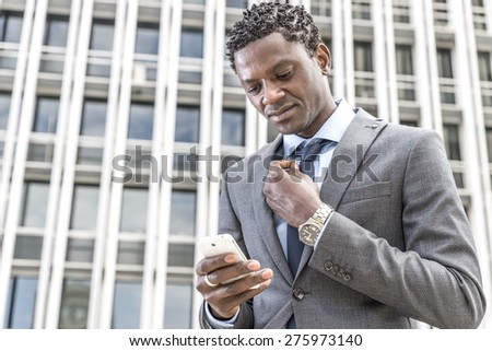 Handsome african american businessman reading email on smart phone. Behind building with windows. - stock photo