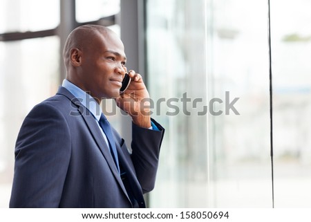 handsome african american businessman talking on mobile phone in modern office - stock photo