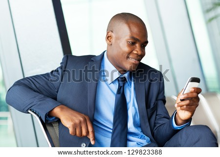 handsome african american businessman using smart phone emailing - stock photo