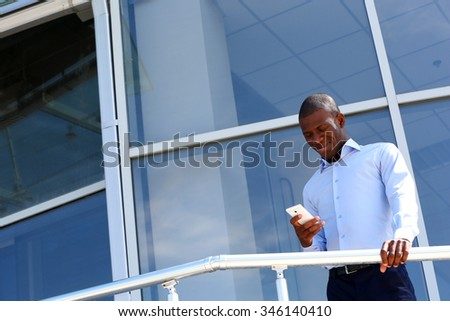 Handsome African American businessman with mobile phone near business centre - stock photo