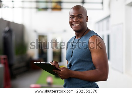 handsome african american male trainer with clipboard - stock photo