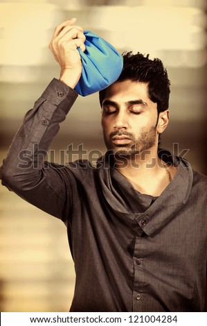 Handsome African American man using an ice pack for a headache - stock photo