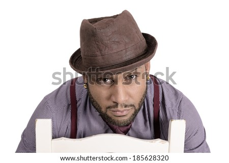 Handsome African American young man in hat sitting and looking at camera. Copy space - stock photo