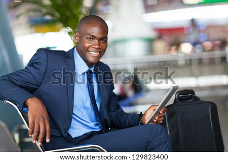 handsome african businessman using tablet computer in airport - stock photo