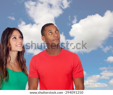 Handsome african guy and his caucasian girl looking up with a blue sky of background - stock photo
