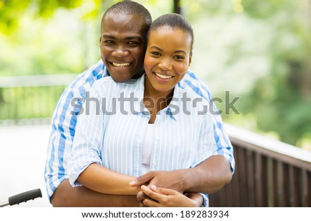 handsome african man hugging girlfriend outdoors - stock photo