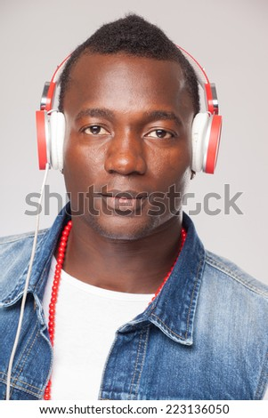 Handsome African man listening to music on DJ headphones - stock photo