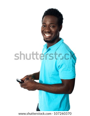 Handsome african man using cellphone, smiling and looking at camera