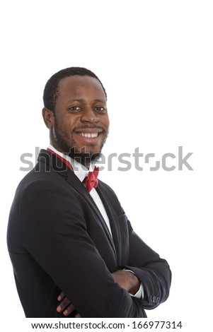 Handsome African man with a beaming smile wearing a natty red bow tie standing with folded arms looking sideways at the camera, isolated on white