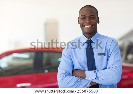 handsome african man working at car dealership - stock photo