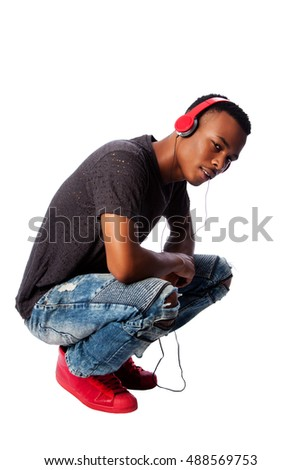 Handsome African teenager listening to music wearing red headphones while squatting, on white.