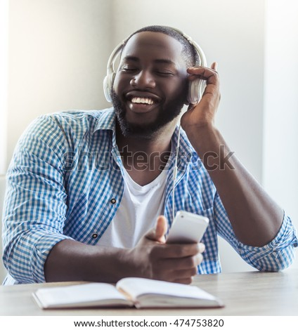 Handsome Afro American businessman in casual clothes and headphones is listening to music using a smart phone and smiling while sitting at home