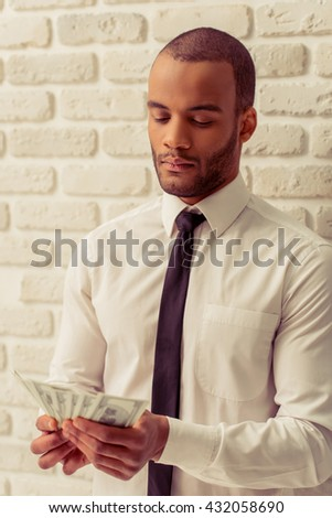 Handsome Afro American businessman in classic shirt and tie holding banknotes, standing against white brick wall - stock photo