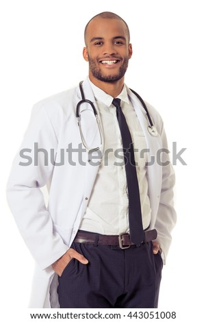 Handsome Afro American doctor in white coat is looking at camera and smiling while standing with hands in pockets, isolated on white background