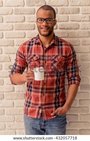 Handsome Afro American man in casual clothes and eyeglasses is holding a cup of drink, looking at camera and smiling, against white brick wall - stock photo