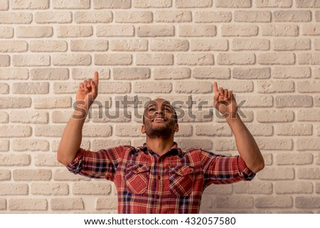Handsome Afro American man in casual clothes is smiling, pointing and looking up, against white brick wall - stock photo