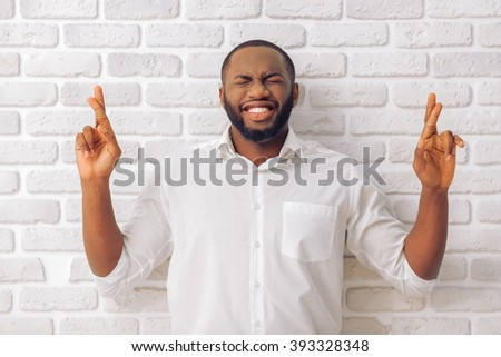 Handsome Afro American man in classic shirt is keeping fingers crossed, standing against white brick wall - stock photo