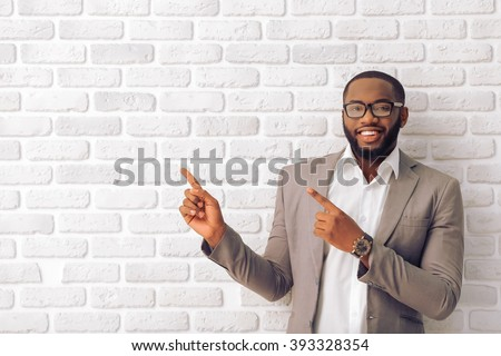 Handsome Afro American man in classic suit and glasses is smiling, looking at camera and pointing away, against white brick wall - stock photo