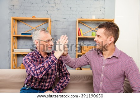 Handsome aged father  giving a high five to his  son - stock photo