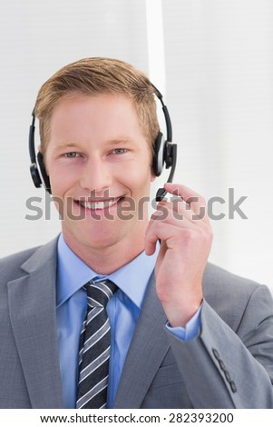 Handsome agent wearing headset in call center - stock photo