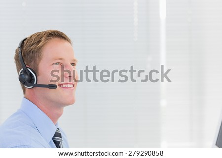 Handsome agent with headset in call center - stock photo