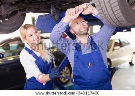 Handsome american mechanic and female assistant working at auto repair shop - stock photo