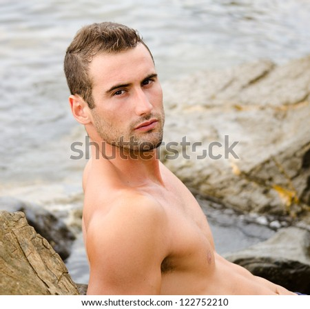 Handsome and athletic shirtless young man on sea rocks looking at camera - stock photo