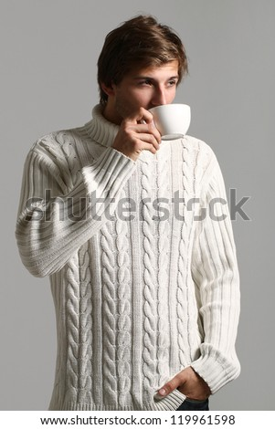 Handsome and beautiful man in white sweater drinking tea - stock photo