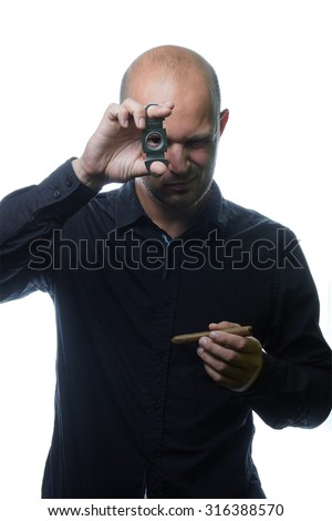 handsome and brutal man with cigar cutter and a cigar