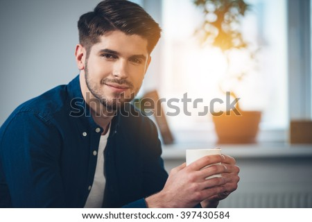 Handsome and calm. Close-up part of handsome young man holding coffee cup with smile and looking at camera while sitting on the couch at home - stock photo
