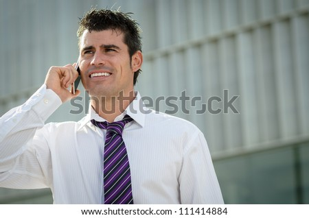 Handsome and cheerful businessman talking by phone in front of his company building - stock photo