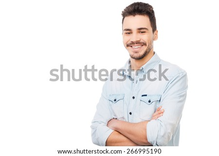 Handsome and cheerful. Handsome young man in shirt looking at camera and keeping arms crossed while standing against white background  - stock photo