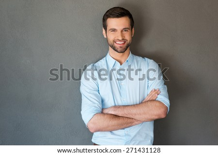 Handsome and confident. Handsome young man in shirt keeping arms crossed and smiling at camera while standing against grey background  - stock photo