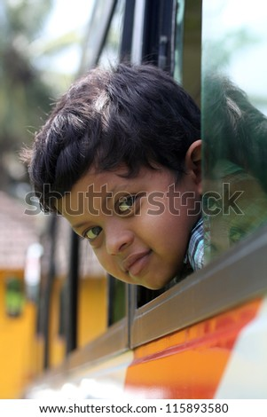 Handsome and cute little indian school kid looking back with happiness from the window of a school bus. The face shows the innocence and childishness of the 6 year old boy with a smile on his face - stock photo