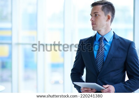 Handsome and elegant businessman with digital tablet posing in isolation - stock photo
