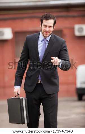 handsome and expresive businessman walking on the street with a briefcase - stock photo