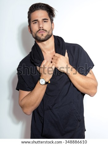 handsome and fit young man in casual outfit posing with wrist watch - stock photo