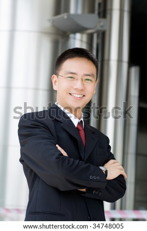 Handsome and good looking asian business man smiling - stock photo