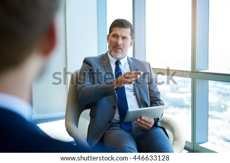 Handsome and mature corporate leader, sitting in a modern office space with large windows, giving valuable advice to a younger colleague while holding a digital tablet - stock photo