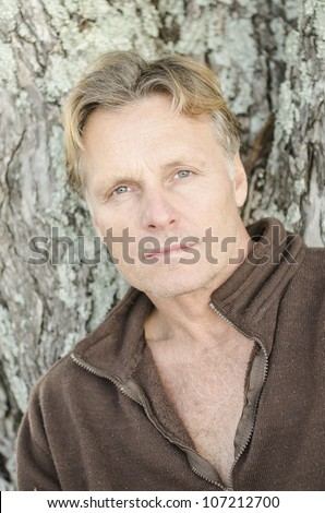handsome and 	pensive looking man in his forties looking at camera - stock photo