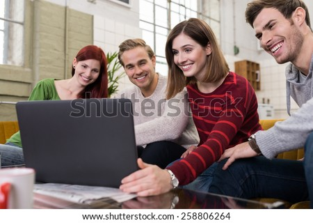 Handsome and Pretty Young White Friends Sitting on the Couch, Watching Something at Laptop Computer Happily. - stock photo