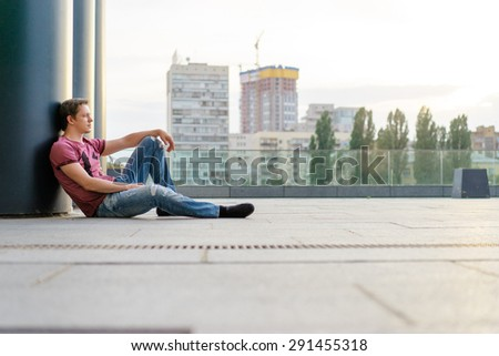 Handsome and relaxed. Young man in casual wear sitting on the floor outdoors. - stock photo