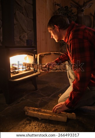 handsome and rugged man stoking wood stove fire