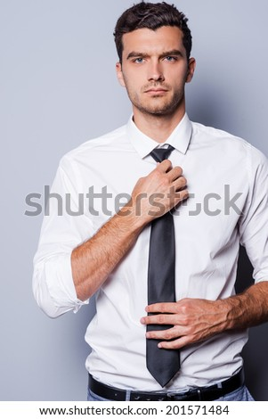 Handsome and self-confident. Handsome young man in formalwear adjusting his necktie and looking at camera while standing against grey background - stock photo