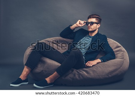 Handsome and stylish. Confident young handsome man adjusting his sunglasses and looking away while sitting on beanbag against grey background - stock photo