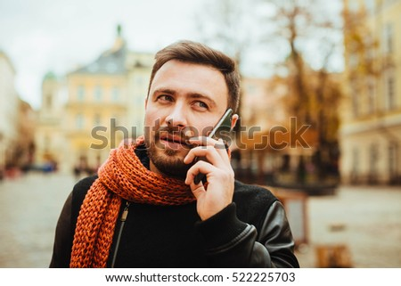 handsome and young man in a black coat speaks by phone outdoors