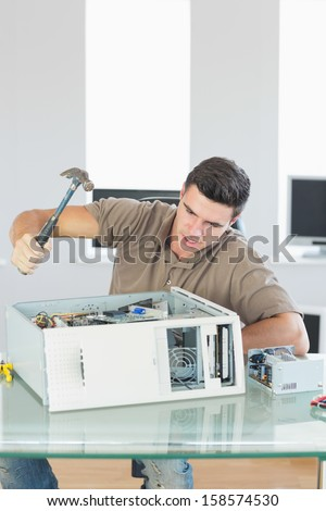 Handsome angry computer engineer destroying computer with hammer in bright office